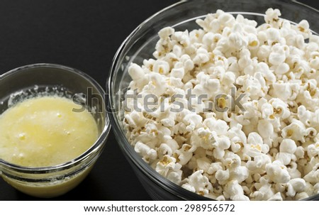 A bowl of freshly popped popcorn and a small dish filled with melted butter