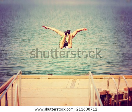 a boy jumping of an old dock into a pond toned with a retro vintage instagram filter  - stock photo
