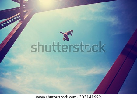 a boy jumping off an old train trestle bridge into a river done with a retro vintage instagram filter (SHALLOW DOF) - stock photo