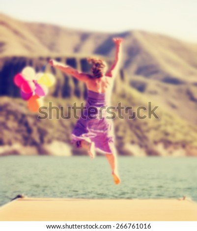 a carefree young woman jumping on a dock with balloons toned with a retro vintage instagram filter effect app or action  - stock photo