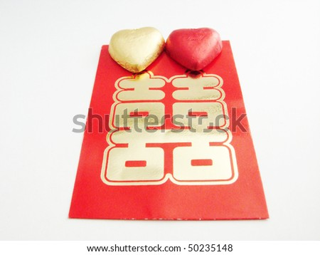 A Chinese double happiness red packet with two heart shape candy. - stock photo