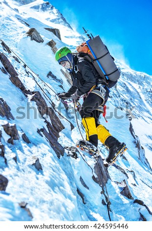 A climber reaching the summit of the mountain Everest - stock photo