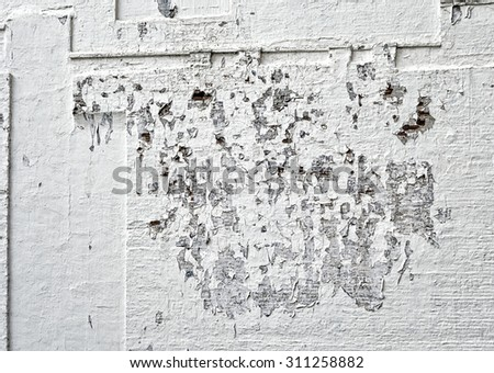 A concrete wall over bricks with holes and peeling paint.
