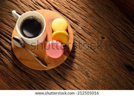A cup of coffee and pastries on old wooden table - stock photo