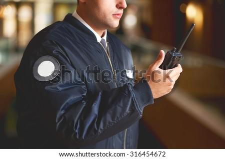 a cut face close up in a security guard with a portable wireless transceiver on a blurry background - stock photo