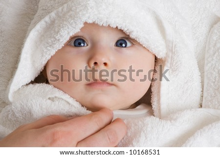 A cute baby wrapped in a towel. - stock photo