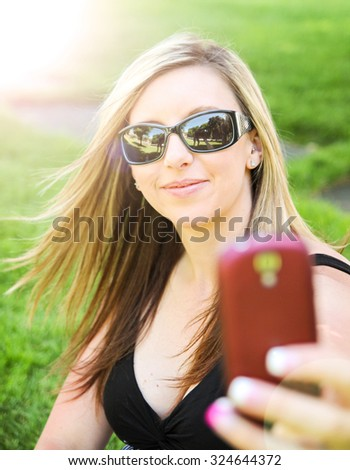 a cute girl smiling at the camera while taking a selfie (self portrait)  - stock photo