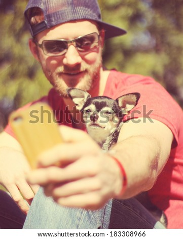 a cute guy smiling at the camera on a bright sunny day done with a retro vintage instagram filter  (very shallow depth of field on the dog's nose)  - stock photo