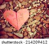 a discarded paper heart on a rock background toned with a retro vintage instagram filter effect  - stock