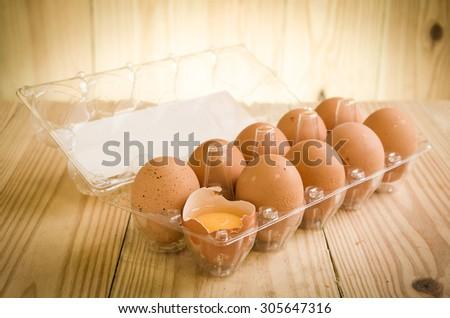 A dozen of eggs in carton, one broken and exposing the yolk - stock photo