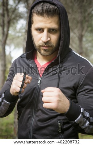 a fit young man in an aggressive pose with raised arms - stock photo