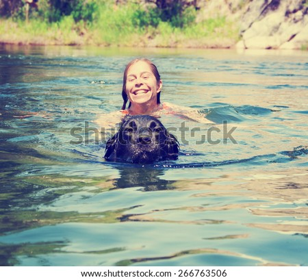 a girl and a big lab dog swimming in the water toned with a retro vintage instagram filter effect app or action  - stock photo