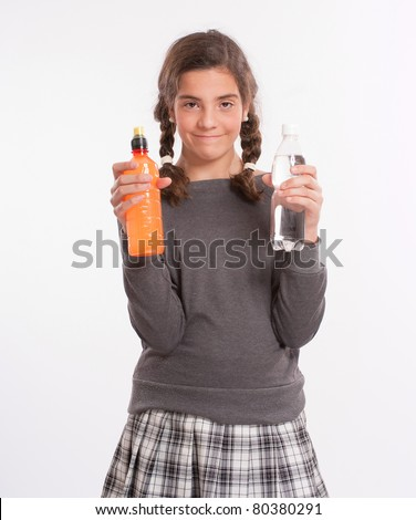 A girl holding a bottle in each hand, one with water, the other a bright orange beverage - stock photo