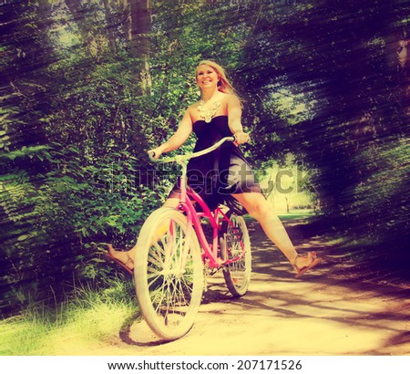 a girl riding a bike on a path in a park full of trees toned with a retro vintage instagram filter and a motion blur  - stock photo