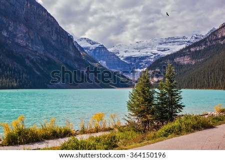 A great sunny day. Rocky Mountains, Canada, Banff National Park. Magnificent Lake Louise with emerald water surrounded by glaciers - stock photo