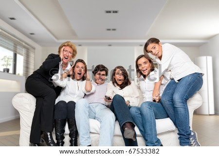 A group of family members sitting at home watching nervously a match - stock photo