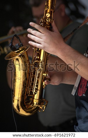 A hand is seen playing a saxophone jazz music