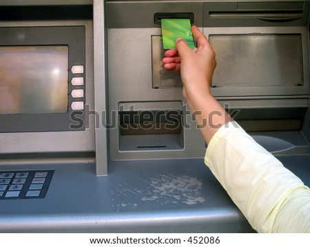 a hand with a credit card at the ATM, trying to get some money. - stock photo