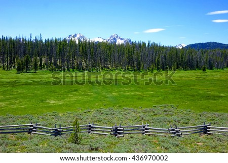 A high mountain meadow is enclosed by a crooked-rail fence. Idaho's Sawtooth Mountains are seen in the background.                              - stock photo