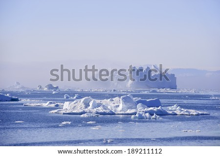 A huge, castle like iceberg, floats in Disko bay. These icebergs are calved by the Jakobshavn glacier, and usually float North with the currents, eventually turning south and down into the Atlantic - stock photo