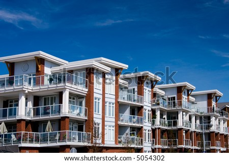 A large apartment building and a blue sky. - stock photo