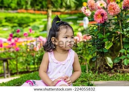 a little baby girl in garden - stock photo