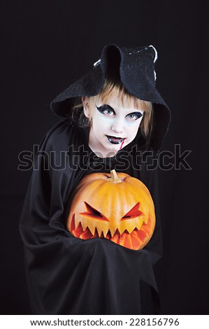 A little girl in a fancy dress with her face painted in Gothic/Vampire style holds Pumpkin