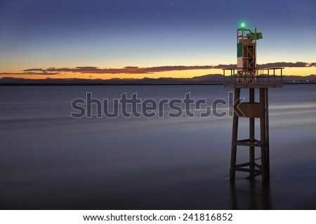 A long exposure of a marine navigation aid near the mouth of the Fraser River. Georgia Strait and Vancouver Island in the background. British Columbia, Canada, near Vancouver. - stock photo