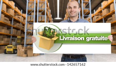 A man holding a Livraison gratuite board, meaning free delivery in French,  in a distribution warehouse - stock photo