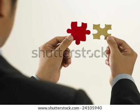 a man try to solve mismatching puzzle - stock photo