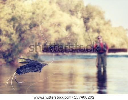 a person fly fishing in a river with a fly in the foreground vintage toned  - stock photo