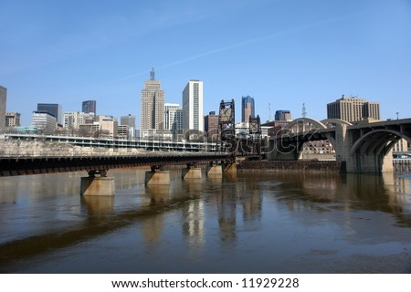 A picture of two bridges converging into St. Paul skyline