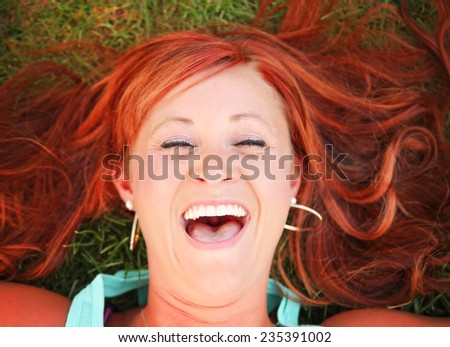 a pretty woman lying in green grass laughing toned with a retro vintage instagram filter  - stock photo