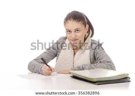 a pretty young woman writing on her desk