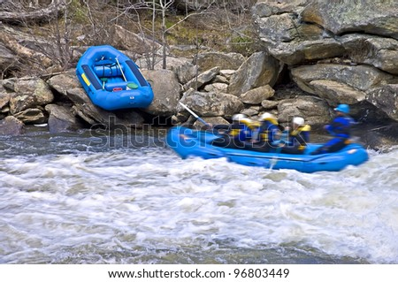 A raft of people in the rapids passing large rocks. Bull Sluice Rapid, part of the Chattooga River on the border of Georgia and South Carolina. - stock photo