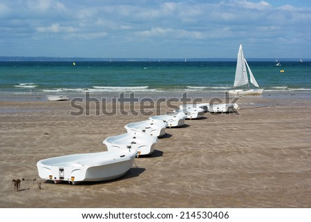 A Row of small training boats of a sail school on the beach of Pleneuf-Val-Andre in Brittany, France - stock photo