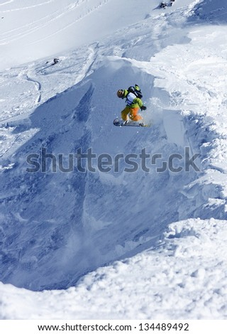 A snowboarder jumping off the ridge