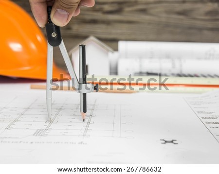 A stationery over blurred architectural blueprint of office building - stock photo