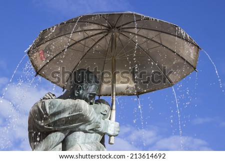 A statue of kissing students under umbrella near the town hall in Tartu, Estonia - stock photo