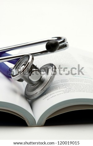 A stethoscope is lying on an open book