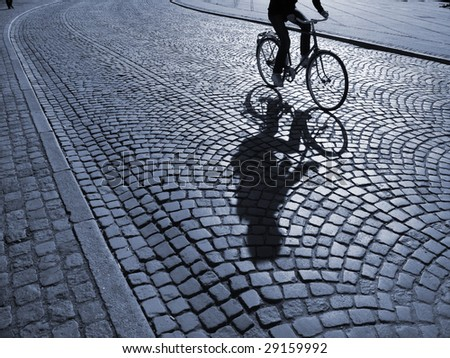 A warm spring afternoon a young man is biking through the old streets of Copenhagen, Denmark. - stock photo