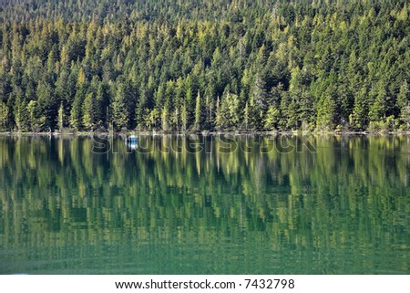 A white boat on the lake surrounded by a dense wood - stock photo