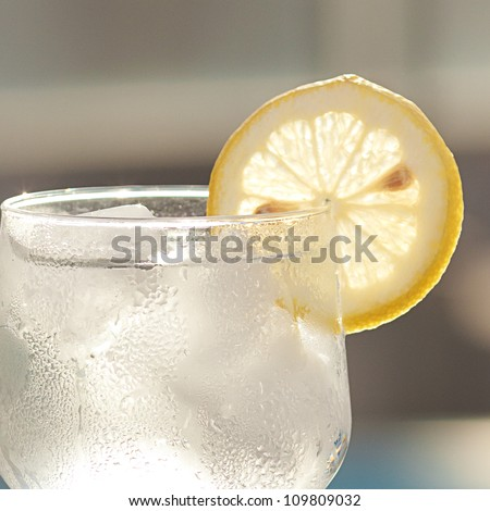 a wine glass with ice and  lemon - stock photo