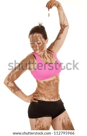 A woman covered in mud with it dripping from her fingertips. - stock photo