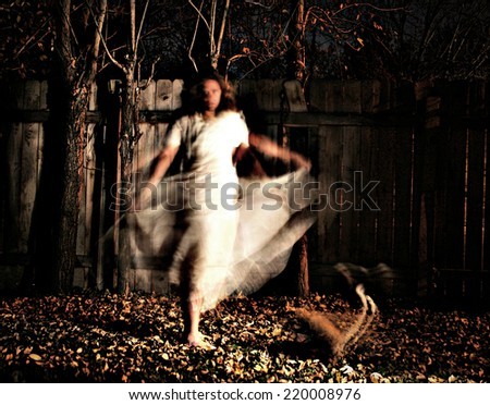 a woman in a very foggy forest at night with a yellow cat and motion blur caused by slow shutter speed with a grainy filter applied  - stock photo