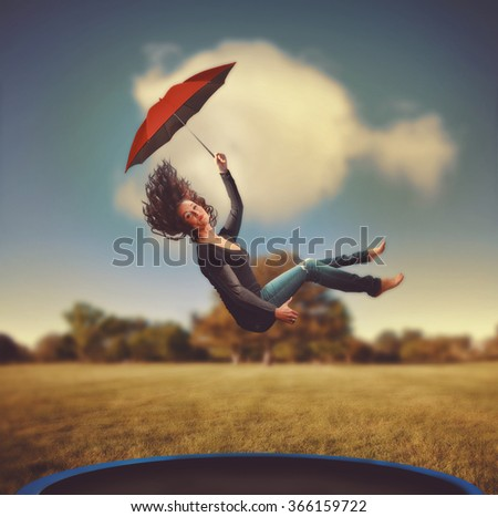 a woman jumping on a trampoline in a park during summer toned with a retro vintage instagram effect app or action - stock photo