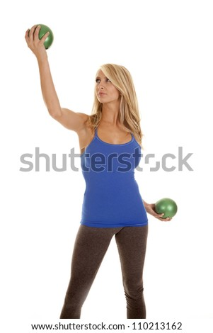 A woman working out with green weights in her hand with a serious expression on her face.