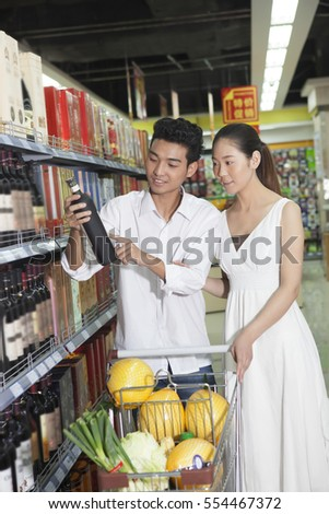 A young couple in the supermarket to buy wine