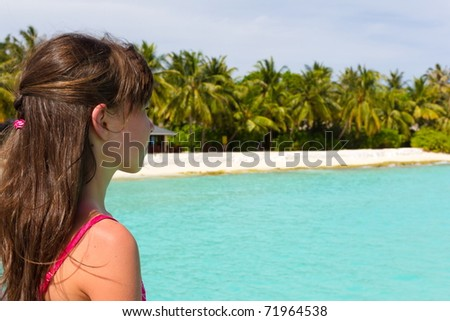 A young girl looking toward a tropical beach with white sand, palm trees and clear blue water.