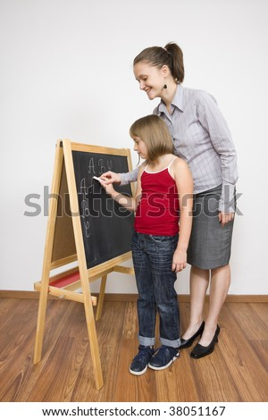 A young teacher and a little child posing, the teacher helping the little pupil to learn to write. - stock photo